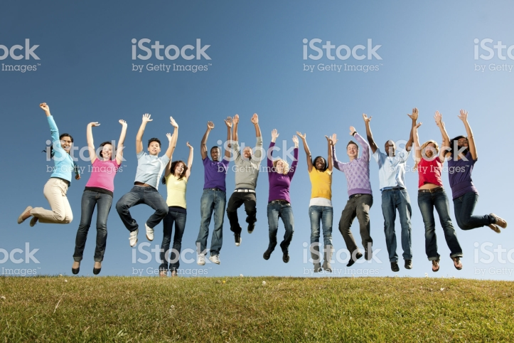 A large group of vibrant young adults outside with a sky background