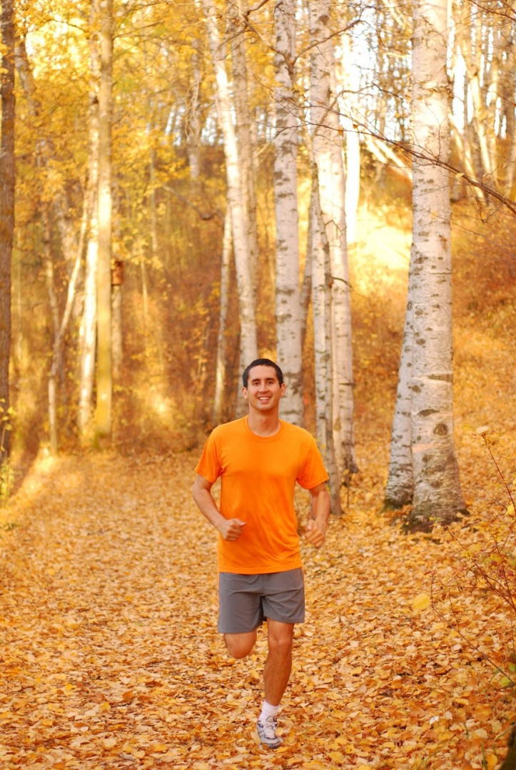 A young man running in the fall.